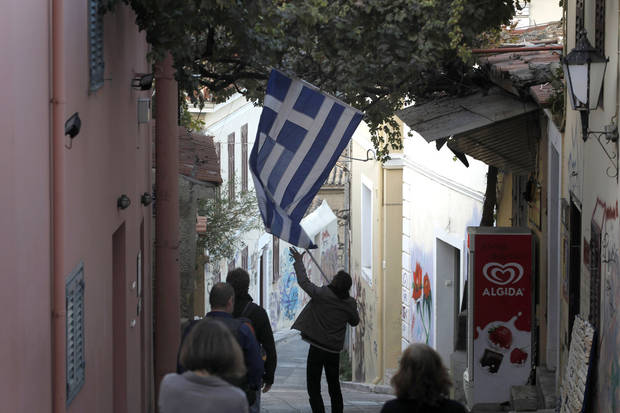 A shopowner unhooks a Greek flag as he prepares to shut down for the evening in the Plaka area of central  Athens, on Tuesday, Nov. 1, 2011. Markets plunged Tuesday and Greece's beleaguered Socialist government faced collapse, a day after Prime Minister George Papandreou unexpectedly announced plans to hold a referendum on the latest international debt relief and bailout deal for his country. (AP Photo/Petros Giannakouris) ORG XMIT: ATH105