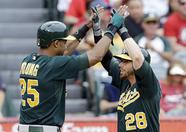 Oakland Athletics' Chris Young, left, and Eric Sogard celebrate as both score on Sogard's home run against the Los Angeles Angels in the third inning of a baseball game in Anaheim, Calif., Sunday, July 21, 2013. (AP Photo/Reed Saxon)
