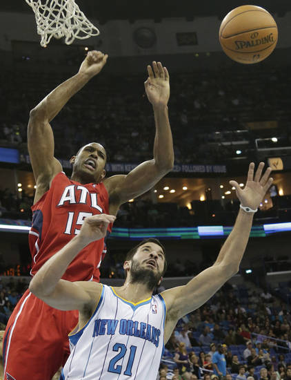 New Orleans Hornets point guard Greivis Vasquez (21) and Atlanta Hawks center Al Horford (15) fight for a rebound during the second quarter of an NBA basketball game at the New Orleans Arena in New Orleans Tuesday, Jan. 1, 2013. (AP Photo/Dave Martin)