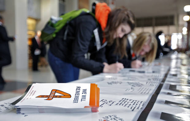 Oklahoma State sophomores Holly Vetsch and Madison Anders, from left, sign the memory banner during the memorial service for Oklahoma State head basketball coach Kurt Budke and assistant coach Miranda Serna at Gallagher-Iba Arena on Monday, Nov. 21, 2011 in Stillwater, Okla. The two were killed in a plane crash along with former state senator Olin Branstetter and his wife Paula while on a recruiting trip in central Arkansas last Thursday. Photo by Chris Landsberger, The Oklahoman