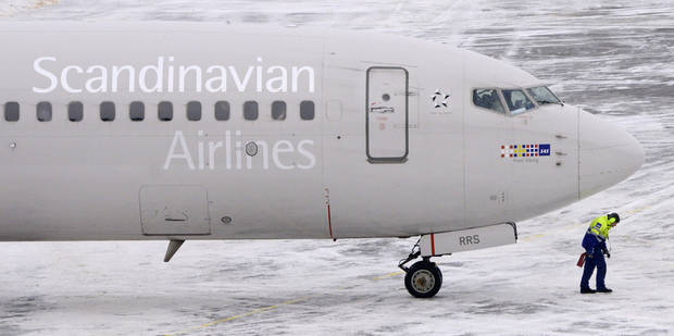 An airport worker walks away from an SAS Boeing 737 aircraft after it was pushed back from the terminal at Arlanda airport, north of Stockholm, Sweden, Wednesday, Dec. 12, 2012. Struggling Scandinavian airline SAS AB, which last month announced an aggressive cost-cutting plan in a final desperate attempt to avoid bankruptcy, reported a 3 billion kronor ($450 million) full-year loss on Wednesday. (AP Photo/Scanpix, Johan Nilsson) SWEDEN OUT