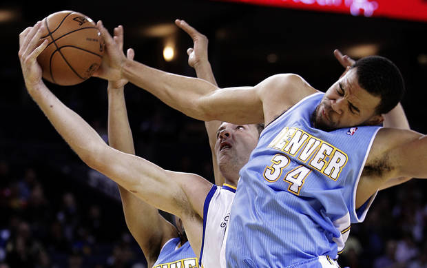 Denver Nuggets' JaVale McGee (34) blocks the shot of Golden State Warriors' David Lee during the first half of an NBA basketball game Saturday, Nov. 10, 2012, in Oakland, Calif. (AP Photo/Ben Margot)