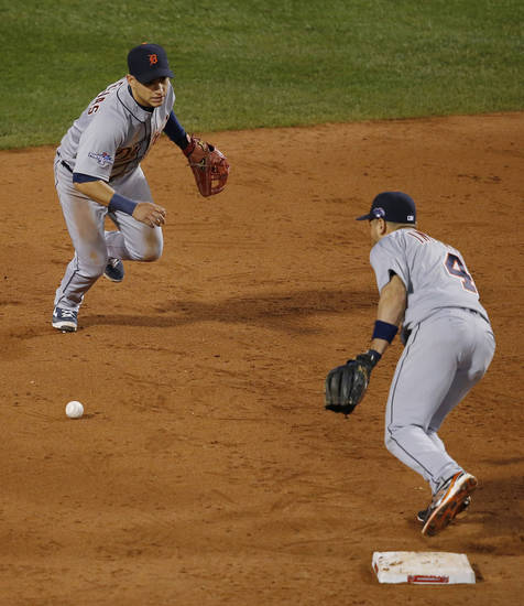 Detroit Tigers shortstop Jose Iglesias, left, can't make a play on a ball hit by Boston Red Sox's Jacoby Ellsbury in the seventh inning during Game 6 of the American League baseball championship series on Saturday, Oct. 19, 2013, in Boston. At right is Tigers second baseman Omar Infante. (AP Photo/Elise Amendola)