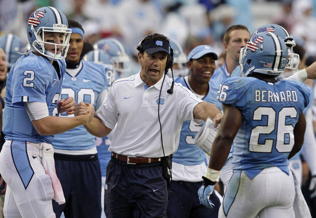 North Carolina head coach Larry Fedora congratulates quarterback Bryn Renner (2) and Giovani Bernard (26) following Bernard's touchdown against Idaho during the first half of an NCAA college football game in Chapel Hill, N.C., Saturday, Sept. 29, 2012. (AP Photo/Gerry Broome)