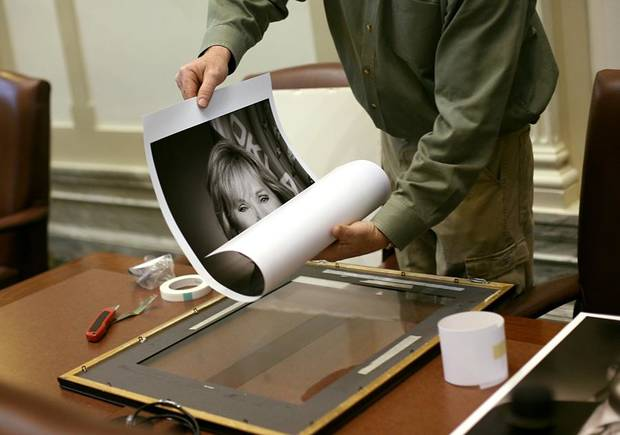 Tim Francis, of FrameMaster Gallery in Edmond, unrolls a portrait of Governor Mary Fallin as he replaces the portrait of former Governor Brad Henry in the House of Representatives Chamber at the Oklahoma State Capitol before the Inauguration of Mary Fallin in Oklahoma City on Monday, Jan. 10, 2011. Photo by John Clanton, The Oklahoman