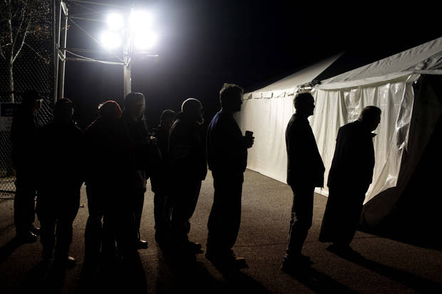 Under the lights of a generator, voters wait in line outside of a tent serving as a polling site in the Midland Beach section of Staten Island, New York, on Election Day Tuesday, Nov. 6, 2012. The original polling site, a school, was damaged by Superstorm Sandy. (AP Photo/Seth Wenig) ORG XMIT: NYSW101