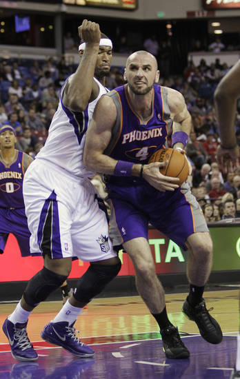 Phoenix Suns center Marcin Gortat, right, of Poland, drives to the basket against Sacramento Kings center DeMarcus Cousins during the first half of an NBA preseason basketball game in Sacramento, Calif., Wednesday, Oct. 10, 2012. (AP Photo/Rich Pedroncelli)