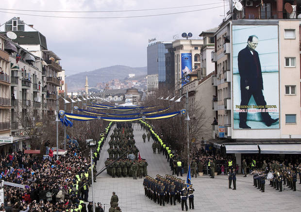 A Kosovo Security Force honor guard leads the parade in the center of Pristina marking the 5th anniversary since Kosovo seceded from Serbia Sunday, Feb. 17, 2013. Serbia rejects Kosovo's independence. Banner on wall at right shows the late Kosovo leader Ibrahim Rugova. (AP Photo/Visar Kryeziu)