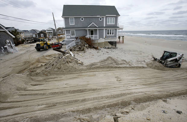 A heavy machine clears the beach Friday, Feb. 22, 2013, in the Normandy Beach section of Dover Township, N.J., of debris left from a home destroyed by Superstorm Sandy. (AP Photo/Mel Evans)