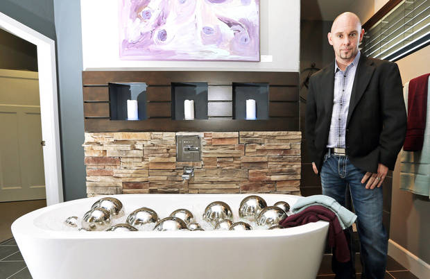 Homebuilder Jeff Click shows the master bathroom at 17320 White Hawk Drive, a model home in the Silverhawk addition.