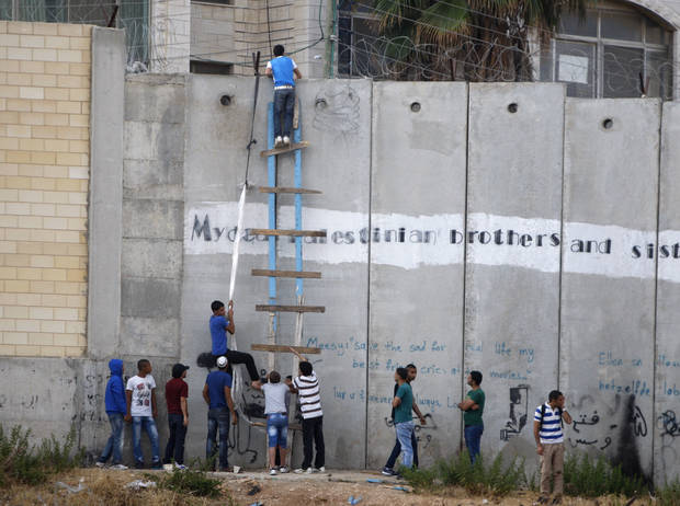 Palestinians use a ladder to climb over the separation barrier with Israel on their way to pray at the Al-Aqsa Mosque in Jerusalem during the Muslim holy month of Ramadan, at Al-Ram, north of Jerusalem, Friday, July 19, 2013. (AP Photo/Majdi Mohammed)