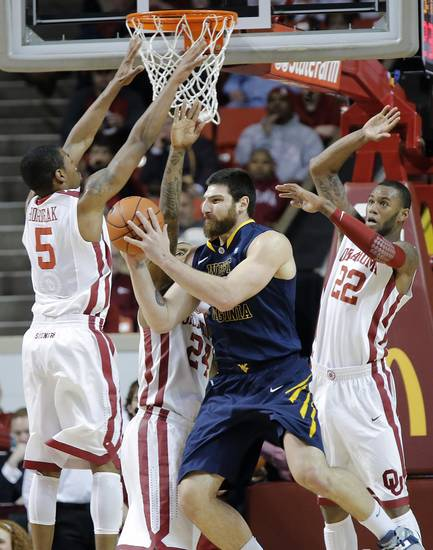 Oklahoma's Je'lon Hornbeak (5), Romero Osby (24) and Amath M'Baye (22) defend on West Virginia 's Deniz Kilicli (13) during the first half of the college basketball game between the University of Oklahoma Sooners (OU) and the West Virginia University Mountaineers (WVU) at the Lloyd Noble Center on Wednesday, March 6, 2013, in Norman, Okla. Photo by Chris Landsberger, The Oklahoman