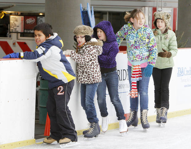 Right: Beginner skaters stay close to the rail during the final weekend of the Edmond Outdoor Ice Skating Rink.
