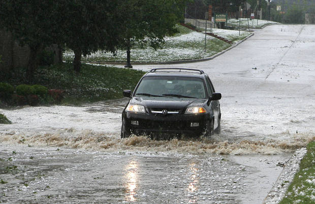 A car passes through flash flood waters in NW Oklahoma City, OK, after a severe thunderstorm moved through the area dumping up to baseball-size hail, Sunday, May 16, 2010. By Paul Hellstern, The Oklahoman
