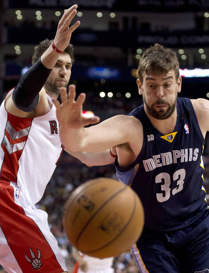 Memphis Grizzlies center Marc Gasol (33) and Toronto Raptors forward Andrea Bargnani chase down a loose ball during the first half of an NBA basketball game in Toronto on Wednesday, Feb. 20, 2013. (AP Photo/The Canadian Press, Frank Gunn)