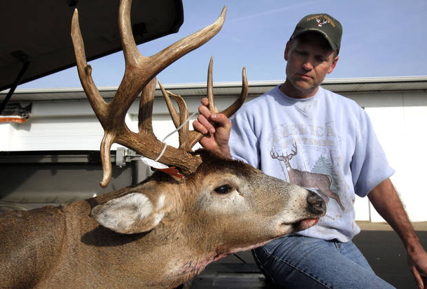 Randal Brainerd, of Kalamazoo, Mich. shows off a buck with a double drop tine set of antlers he shot in Alamo Township of the first day of firearm deer season Thursday, Nov. 15, 2012 at the DNR check in Plainwell, Mich.(AP Photo/The Kalamazoo Gazette, Mark Bugnaski) ALL LOCAL TV OUT; LOCAL TV INTERNET OUT