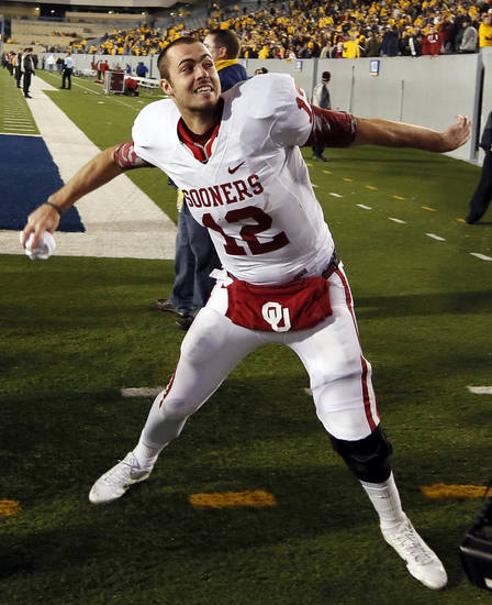Oklahoma's Landry Jones (12) throws a towel to OU fans in the stands after a college football game between the University of Oklahoma and West Virginia University on Mountaineer Field at Milan Puskar Stadium in Morgantown, W. Va., Nov. 17, 2012. OU won, 50-49. Photo by Nate Billings, The Oklahoman