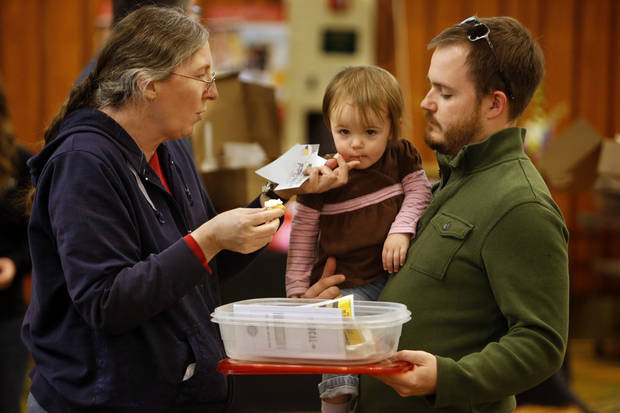 Mary Torres gives grandaughter Evie a sample of chocolate as Evie's father John Stewart carries the goods at the Firehouse Art Center's annual Chocolate Festival on Saturday, Feb. 2, 2013 in Norman, Okla.  Photo by Steve Sisney, The Oklahoman