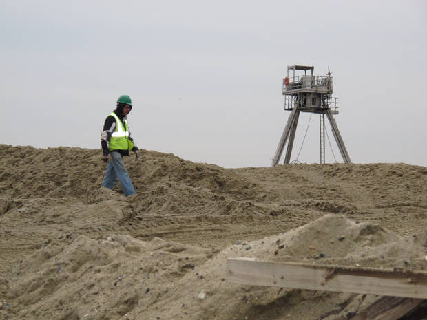 A worker carrying out a beach replenishment project in Sea Bright N.J. on Jan. 15, 2013. The town's entire business district was wiped out by Superstorm Sandy (four shops have since re-opened) and 75 percent of residents are still homeless. Yet Sea Bright is determined to rebuild as a debate rages on whether to restore shore communities to their pre-storm condition, or buy out properties in flood-prone areas and depopulate them. (AP Photo/Wayne Parry)