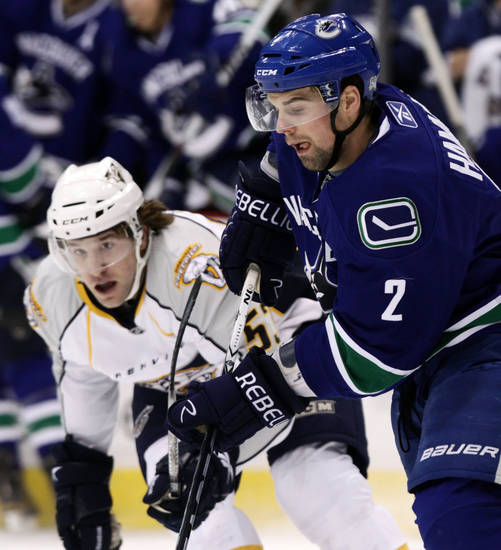 Vancouver Canucks' Dan Hamhuis, right, plays the puck past Nashville Predators' Chris Mueller during the first period of an NHL hockey game in Vancouver, British Columbia, on Wednesday, Jan. 26, 2011. (AP Photo/The Canadian Press, Darryl Dyck)