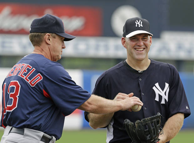 Boston Red Sox third base coach Brian Butterfield, left, puts a ball into the glove of New York Yankees third baseman Kevin Youkilis, a former Red Sox infielder, before a spring training baseball game in Tampa, Fla., Wednesday, March 20, 2013.  (AP Photo/Kathy Willens)