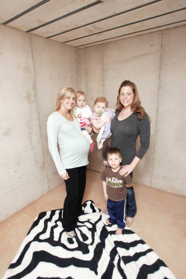 Jessica Daniels and her 17-month-old daughter, Reese, pose with Julie LeBlanc and her daughter Brinklee, 1, and son  Drake, 3, in the safe room of her Oak Tree home in Edmond.  PHOTO BY STEVE GOOCH,  THE OKLAHOMAN