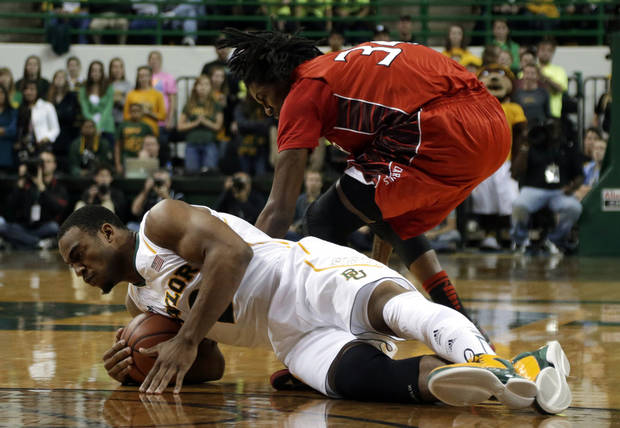 Baylor forward Rico Gathers, bottom, dives to the floor to grab a loose ball in front of Lamar forward Amos Wilson in the first half of an NCAA college basketball game on Wednesday, Dec. 12, 2012, in Waco, Texas. (AP Photo/Tony Gutierrez)