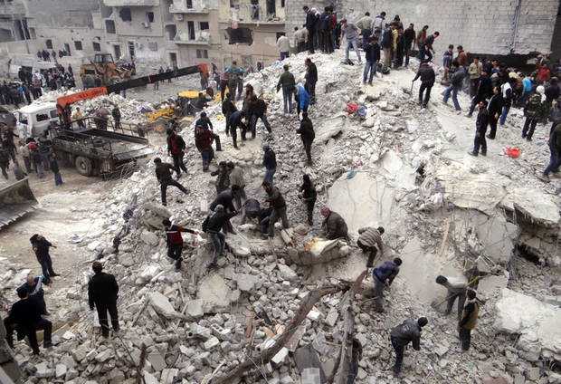 This citizen journalism image provided by Aleppo Media Center, AMC, which has been authenticated based on its contents and other AP reporting, shows people searching  through the debris of destroyed buildings after airstrikes hit the neighborhood of Eastern Ansari, in Aleppo, Syria, Sunday, Feb. 3, 2013. The Britain-based activist group Syrian Observatory for Human Rights, which opposes the regime, said government troops bombarded a building in Aleppo's rebel-held neighborhood of Eastern Ansari that killed over 10 people, including at least five children. (AP Photo/Aleppo Media Center, AMC)