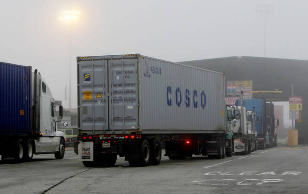 Cargo trucks line up in the dense fog to enter the Port of Long Beach Wednesday December 5, 2012. Work resumed Wednesday at the Los Angeles and Long Beach harbors after settlement of a strike that crippled the nation's busiest container port complex for more than a week. (AP Photo/Nick Ut)