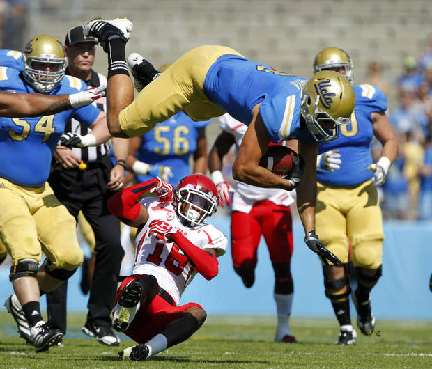 UCLA tight end Joseph Fauria, top, leaps over Utah defensive back Eric Rowe (18) for 12 yards and a first down during the first half of their NCAA college football game, Saturday, Oct. 13, 2012, in Pasadena, Calif. (AP Photo/Alex Gallardo)