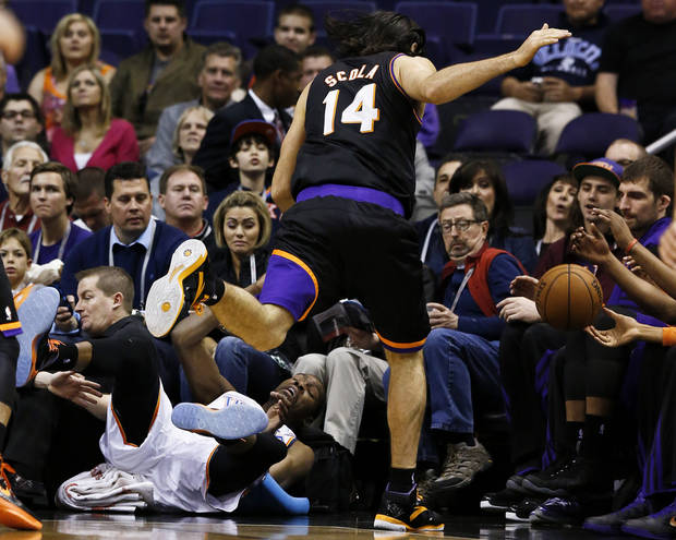 Oklahoma City Thunder's Kevin Durant, bottom left, collides with Phoenix Suns' Luis Scola (14), of Argentina, as both go after a loose ball during the first half in an NBA basketball game, Sunday, Feb. 10, 2013, in Phoenix. (AP Photo/Ross D. Franklin)