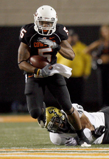 OSU's Keith Toston (5) slips the tackle of Colorado's Anthony Perkins (46) during the college football game between Oklahoma State University (OSU) and the University of Colorado (CU) at Boone Pickens Stadium in Stillwater, Okla., Thursday, Nov. 19, 2009. Photo by Sarah Phipps, The Oklahoman
