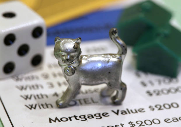 The newest Monopoly token, a cat, rests on a Boardwalk deed next to a die and houses at Hasbro Inc. headquarters, in Pawtucket, R.I., Tuesday, Feb. 5, 2013. Voting on Facebook determined that the cat would replace the iron token. (AP Photo/Steven Senne)