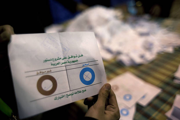 An Egyptian election worker eliminates an invalid ballot while counting ballots at the end of the second round of voting on a referendum on a disputed constitution drafted by Islamist supporters of President Mohammed Morsi at a polling station in Giza, Egypt, Saturday, Dec. 22, 2012. Egypt's Islamist-backed constitution headed toward likely approval in a final round of voting on Saturday, but the deep divisions it has opened up threaten to fuel continued turmoil. (AP Photo/Nasser Nasser)