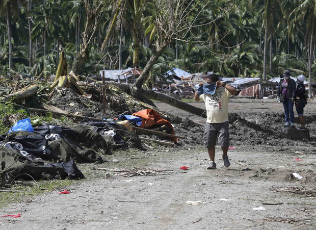 A resident covers his nose as he walks past typhoon Bopha's victims which are left unattended at New Bataan township, Compostela Valley in southern Philippines Saturday Dec. 8, 2012. Search and rescue operations following typhoon Bopha that killed nearly 600 people in the southern Philippines have been hampered in part because many residents of this ravaged farming community are too stunned to assist recovery efforts, an official said Saturday. (AP Photo/Bullit Marquez)