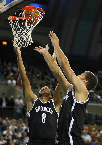 Brooklyn Nets' Deron Williams (8) and Brook Lopez (11) attempt to grab a rebound against the Philadelphia 76ers in the first half during a preseason NBA basketball game, Saturday, Oct. 13, 2012, in Atlantic City, N.J. (AP Photo/Rich Schultz)