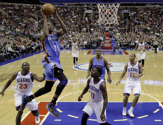 Oklahoma City Thunder's Kevin Durant (35) goes up for a dunk between Philadelphia 76ers' Jason Richardson (23) and Jrue Holiday (11) during the first half of an NBA basketball game, Saturday, Nov. 24, 2012, in Philadelphia. (AP Photo/Matt Slocum) ORG XMIT: PXC108