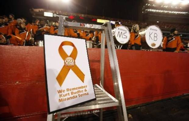 A sign is displayed in front of the Oklahoma State band during a moment of silence Friday, Nov. 18, 2011, honoring Oklahoma State women's basketball coach Kurt Budke and assistant coach Miranda Serna who were killed Thursday in a plane crash, before an NCAA college football game against Iowa State, in Ames, Iowa. (AP Photo/Charlie Neibergall)