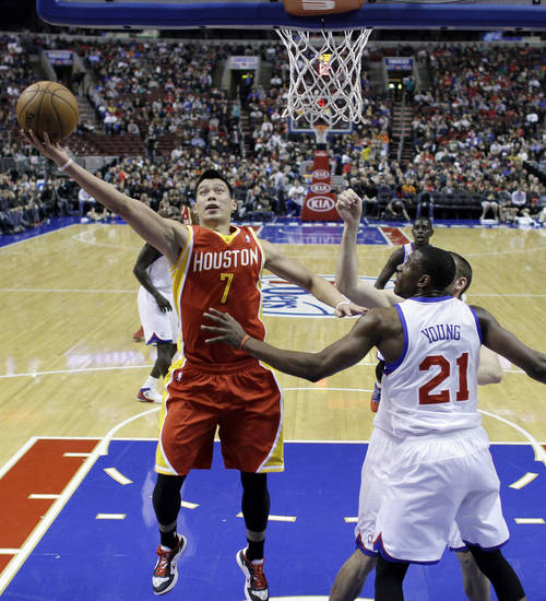 Houston Rockets' Jeremy Lin, left, goes up for a shot against Philadelphia 76ers' Thaddeus Young in the first half of an NBA basketball game, Saturday, Jan. 12, 2013, in Philadelphia. (AP Photo/Matt Slocum)
