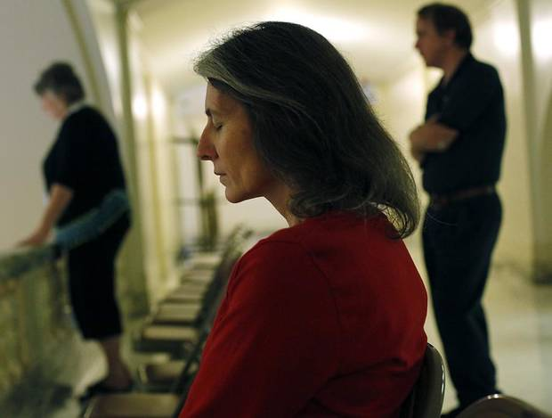 Carol Hardin, of Madill, Okla., (center) bows her head in prayer as she watches the National Day of Prayer from the third floor at the Oklahoma State Capitol in Oklahoma City on May 5, 2011. Photo by John Clanton, The Oklahoman