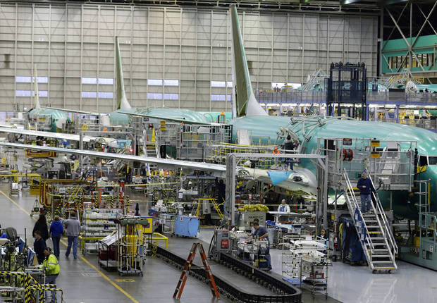 Workers assemble Boeing Co. next-generation 737 airplanes, Tuesday, Jan. 29, 2013 at the company's 737 assembly facility in Renton, Wash. On Jan. 25, 2013, Boeing began assembling next-generation 737 passenger airplanes at an increased rate of 38 planes per month. (AP Photo/Ted S. Warren)