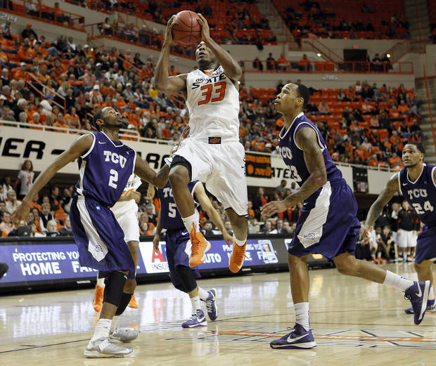 Oklahoma State&#039;s Marcus Smart (33) drives between TCU&#039;s Connell Crossland (2) and Garlon Green (33) during the college basketball game between Oklahoma State University Cowboys (OSU) and Texas Christian University Horned Frogs (TCU) at Gallagher-Iba Arena on Wednesday Jan. 9, 2013, in Stillwater, Okla. 