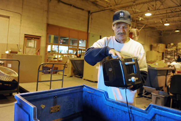 Leon Castillas inspects a toaster that was dropped off as a donation at the Goodwill Donation Center at the Green River Road location in Evansville, Ind. on Wednesday morning, Nov. 28, 2012. Castillas, a veteran of the U.S. Army, is one of the first participants to complete the Vanderburgh County's Veterans Treatment Court this year.    (AP Photo/The Evansville Courier & Press, Erin McCarken)