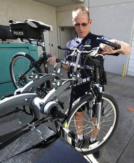 Edmond police Lt. Chuck Linhardt removes his bicycle from his patrol car. Edmond has amended its bicycle ordinance. PHOTO BY PAUL HELLSTERN, THE OKLAHOMAN <strong>PAUL HELLSTERN - THE OKLAHOMAN</strong>