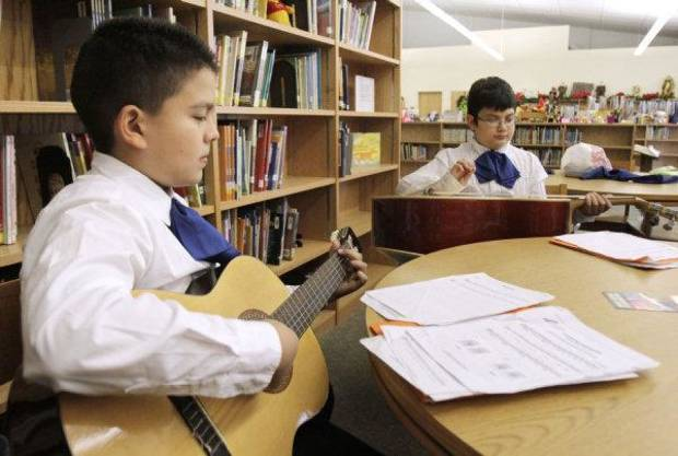 Jorge Jimenez, left, and Gustavo Morales play guitars during a mariachi class Tuesday at Fillmore Elementary School in Oklahoma City. The mariachi program is offered at Fillmore, Capitol Hill and Adams elementary schools. Photo by Paul Hellstern, The Oklahoman <strong>PAUL HELLSTERN</strong>