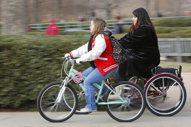 University of Oklahoma students Kendra Kinnamon, left, and Fatima Shakra ride their bikes Monday on the South Oval. Photo By Steve Gooch, The Oklahoman