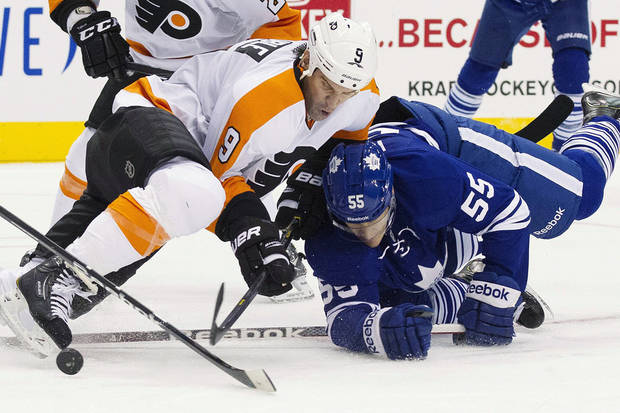 Toronto Maple Leafs' Korbinian Holzer (55) and Philadelphia Flyers' Mike Knuble (9) battle for the puck during the first period of their NHL hockey game, Monday, Feb. 11, 2013, in Toronto. (AP Photo/The Canadian Press, Chris Young)