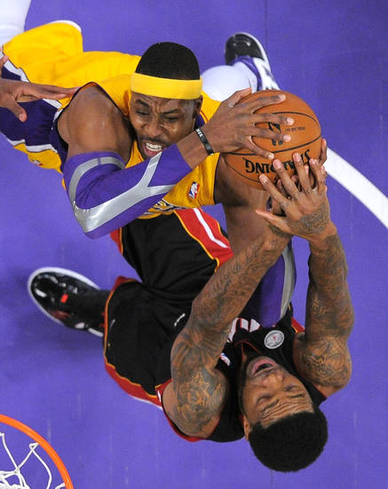 Miami Heat forward Udonis Haslem, below, ties up Los Angeles Lakers center Dwight Howard during the first half of their NBA basketball game on Thursday, Jan. 17, 2013, in Los Angeles. (AP Photo/Mark J. Terrill)