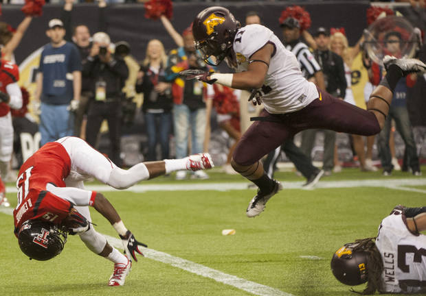 Texas Tech's Derreck Edwards (19) flips into the end zone for a touchdown ahead of Minnesota's Antonio Johnson (11) during the first quarter of the Meineke Car Care Bowl NCAA college football game, Friday, Dec. 28, 2012, in Houston. (AP Photo/Dave Einsel)