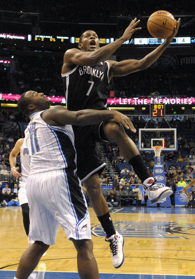 Brooklyn Nets guard Joe Johnson (7) goes up for a shot over Orlando Magic forward Glen Davis during the first half of an NBA basketball game in Orlando, Fla., Friday, Nov. 9, 2012. The Nets won 107-68.(AP Photo/Phelan M. Ebenhack)